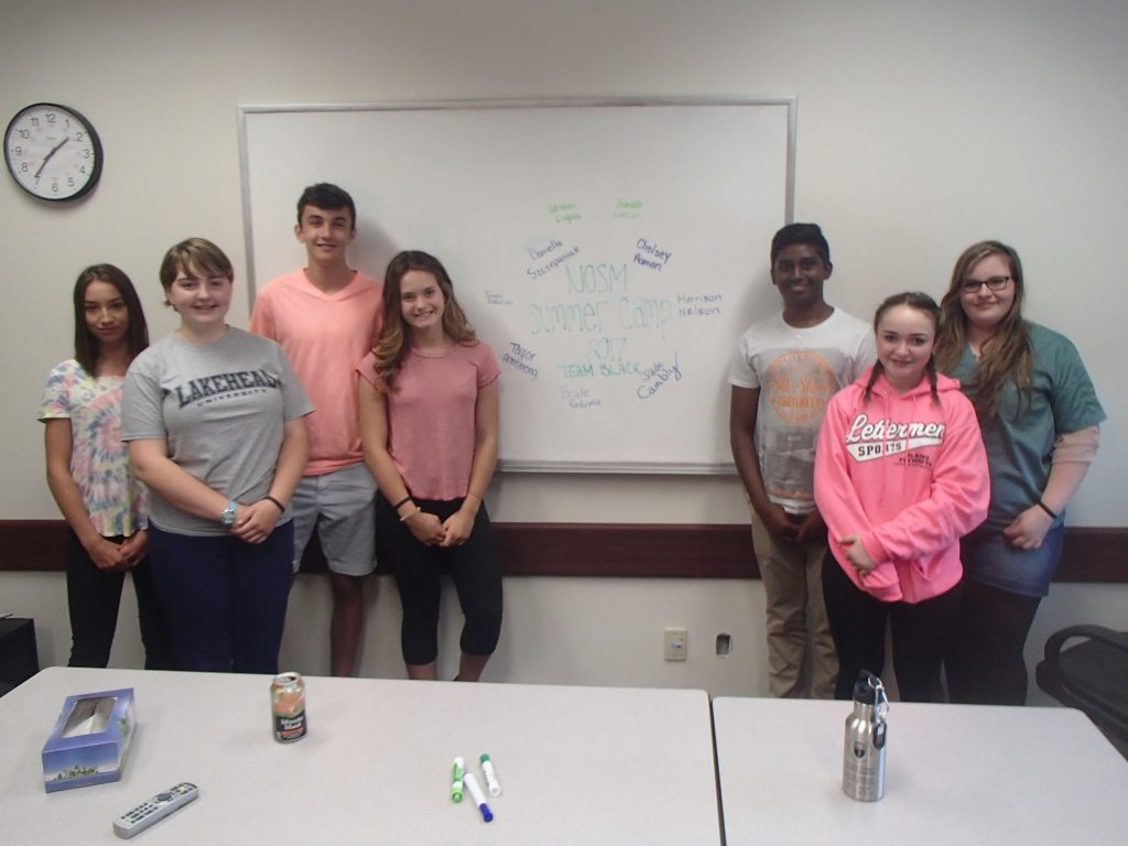 Camper team poses for photo in front of a whiteboard in small group room
