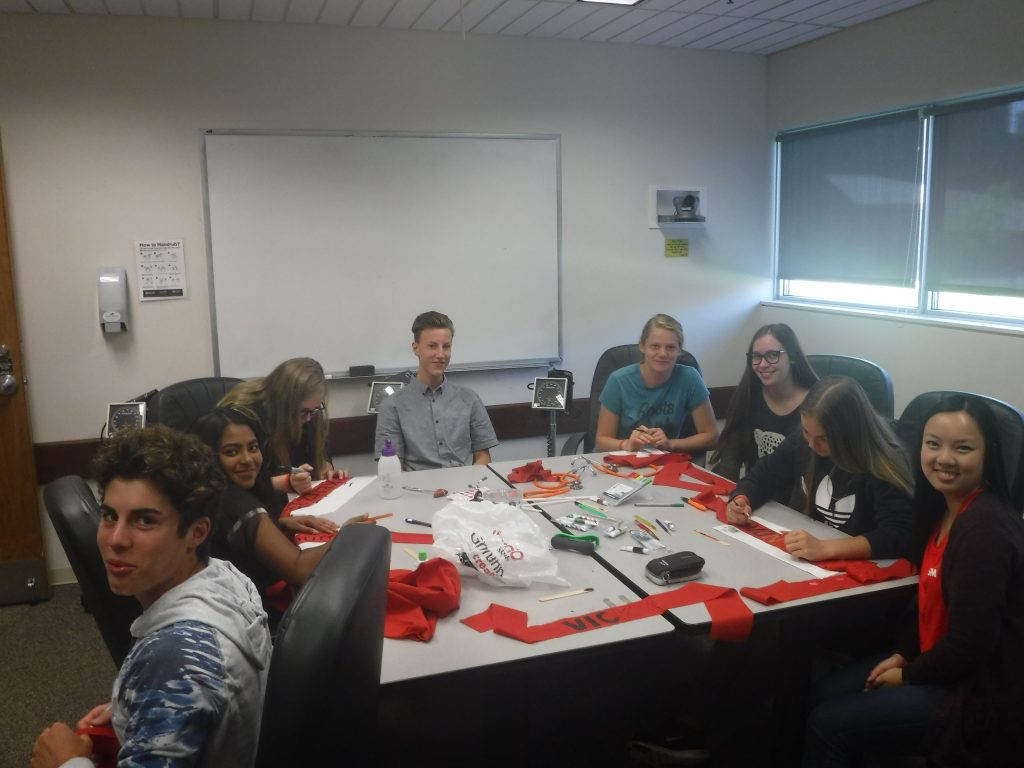 Team Red members prepare red headbands while sitting around table in small group room