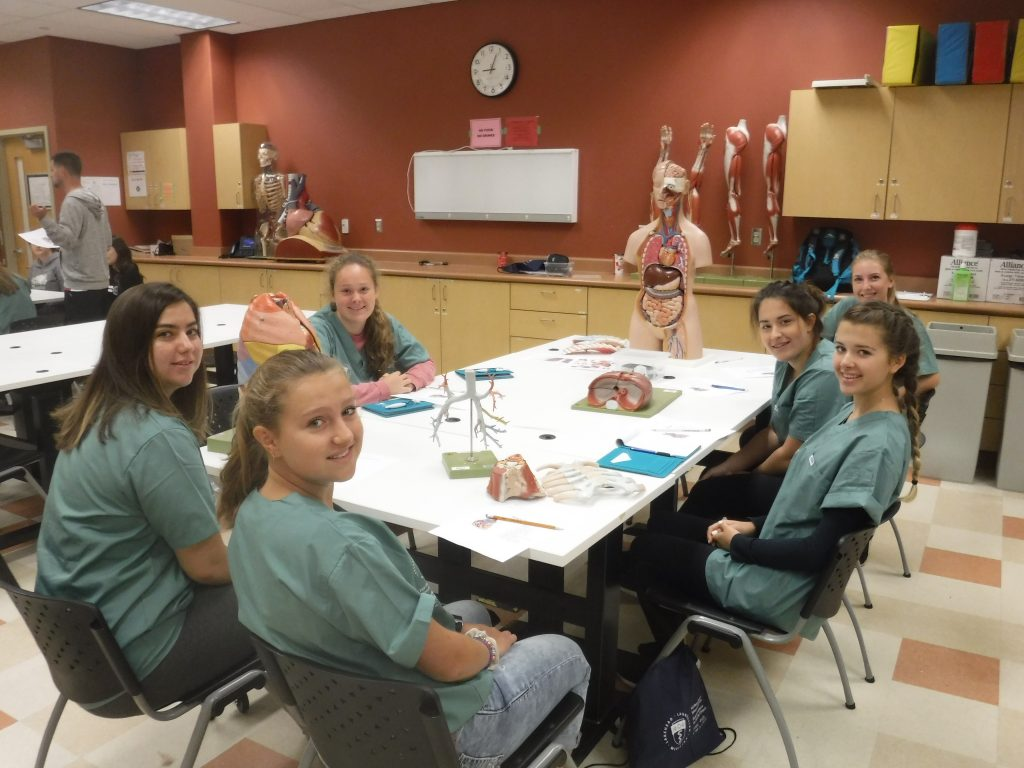 Campers pose for photo during anatomy activity while sitting around table in lab