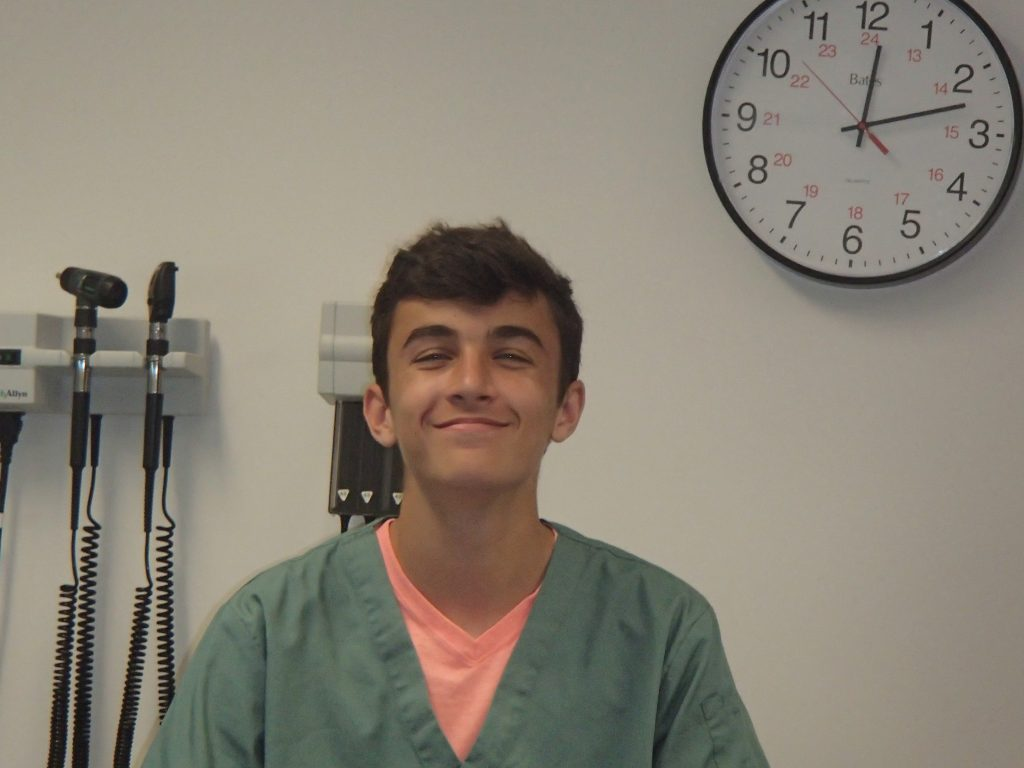 Camper grinning at camera in examination room