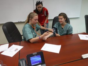 Team lead supervises camper taking the blood pressure of a fellow camper while sitting at table in small group room