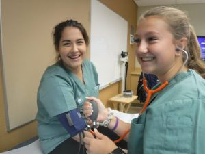 Two campers grin at camera while camper takes blood pressure of other camper using sphygmomanometer (blood pressure cuff) and stethescope