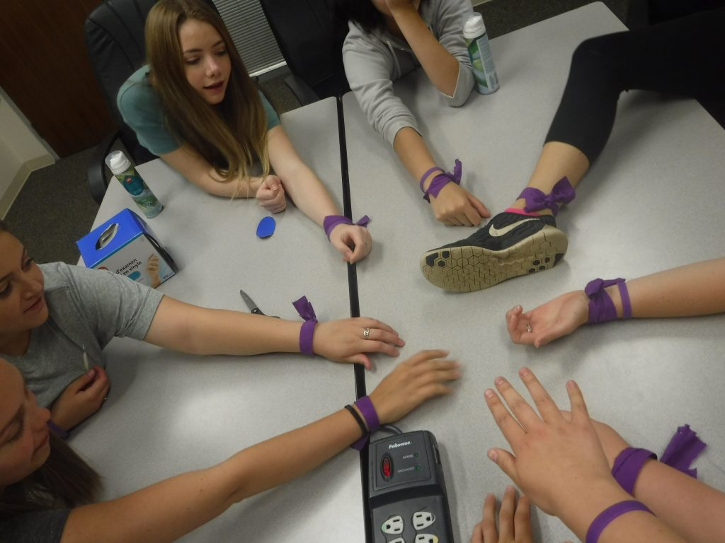 Team purple members display their purple wrist/ankle bands on small group room table
