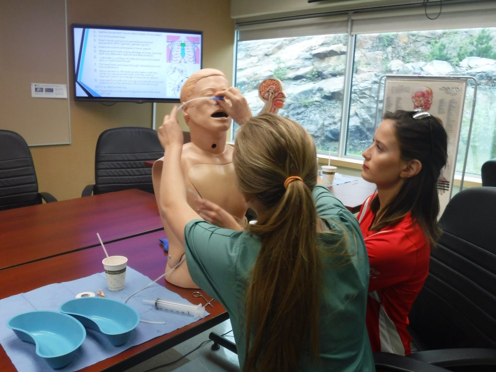 Team lead observes a camper inserting a naso-gastric tube into a SimMan mannequin bust while sitting at table in small group room