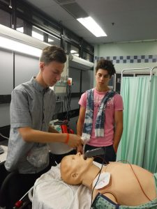 Camper inserts layngoscope into SimMan 3G mannequin while fellow camper looks on