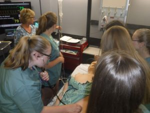Campers practice monitoring vital signs on SimMan 3G mannequin in simulation lab while NOSM staff member supervises