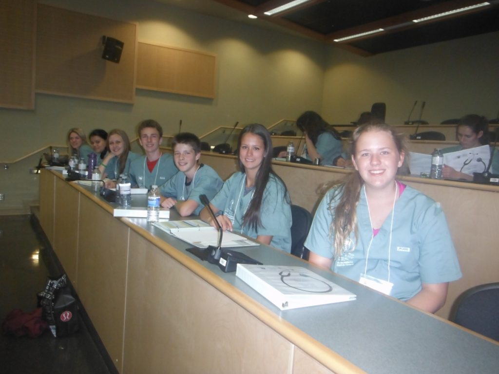 Campers sitting in a row pose for photo in lecture theatre