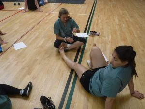 Two campers sit on floor of gymnasium while one camper prepares to tape the other campers ankle