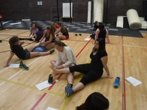 Campers sit on gymnasium floor in pairs for ankle wrapping activity