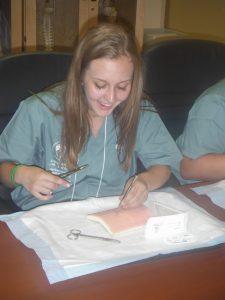 Camper practicing suturing technique
