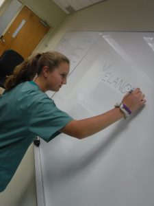 """Camper writes """"melanoma"""" on white board in small group room"""