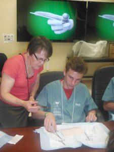 Retired surgeon instructing camper on suturing technique