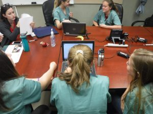 Campers and team lead sit around table in small group room while one camper looks up information on a laptop for Topic Oriented Session discussion