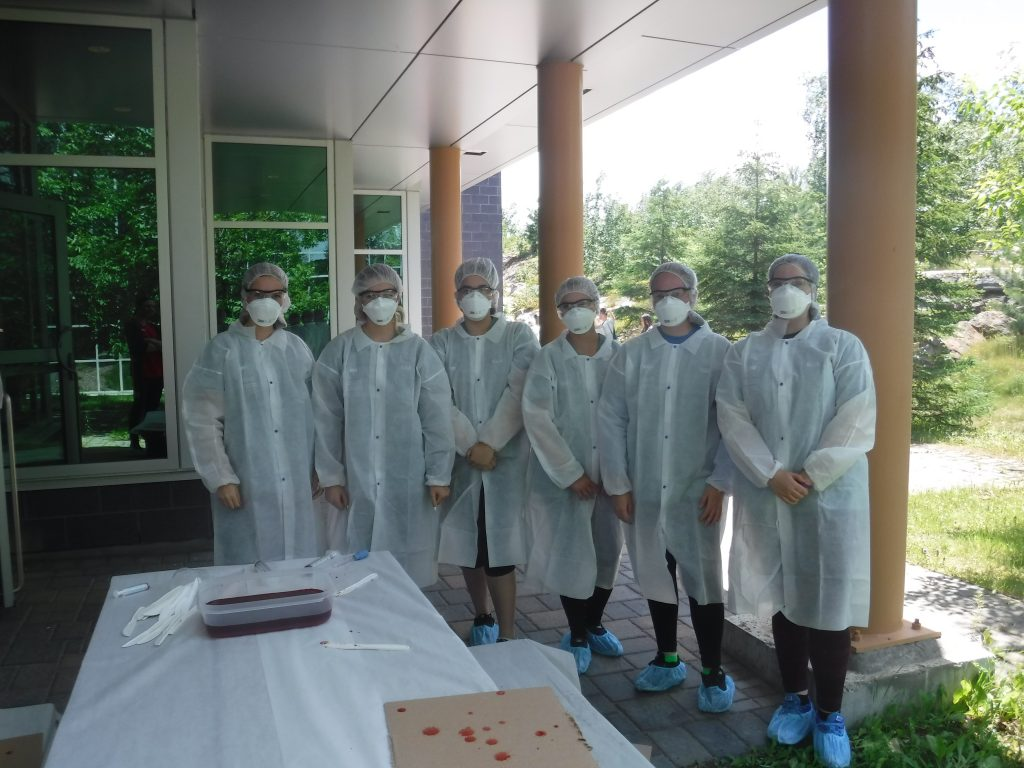 Campers pose for group photo wearing their CSI coats, caps, face masks, glasses, and booties outside medical school building by picnic table