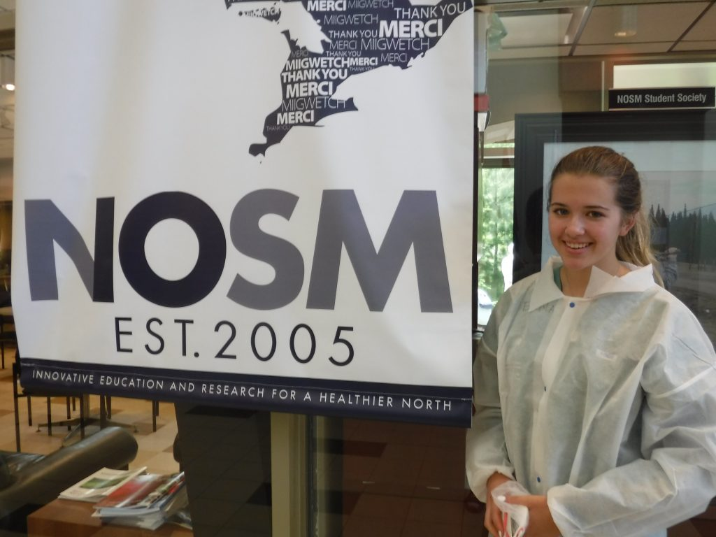 Camper poses for photo beside NOSM Est. 2005 banner in medical school lobby