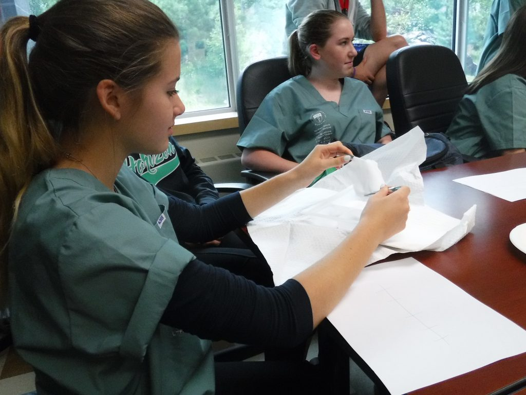 Campers sit around table in small group room while one camper prepares sterilized gauze using tweezers for clinical activity