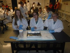 Campers sitting at table in lab pose for photo during dissection activity