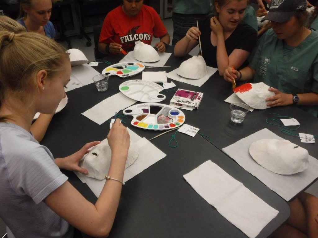 Campers sitting at a table in the lab decorating masks with paint