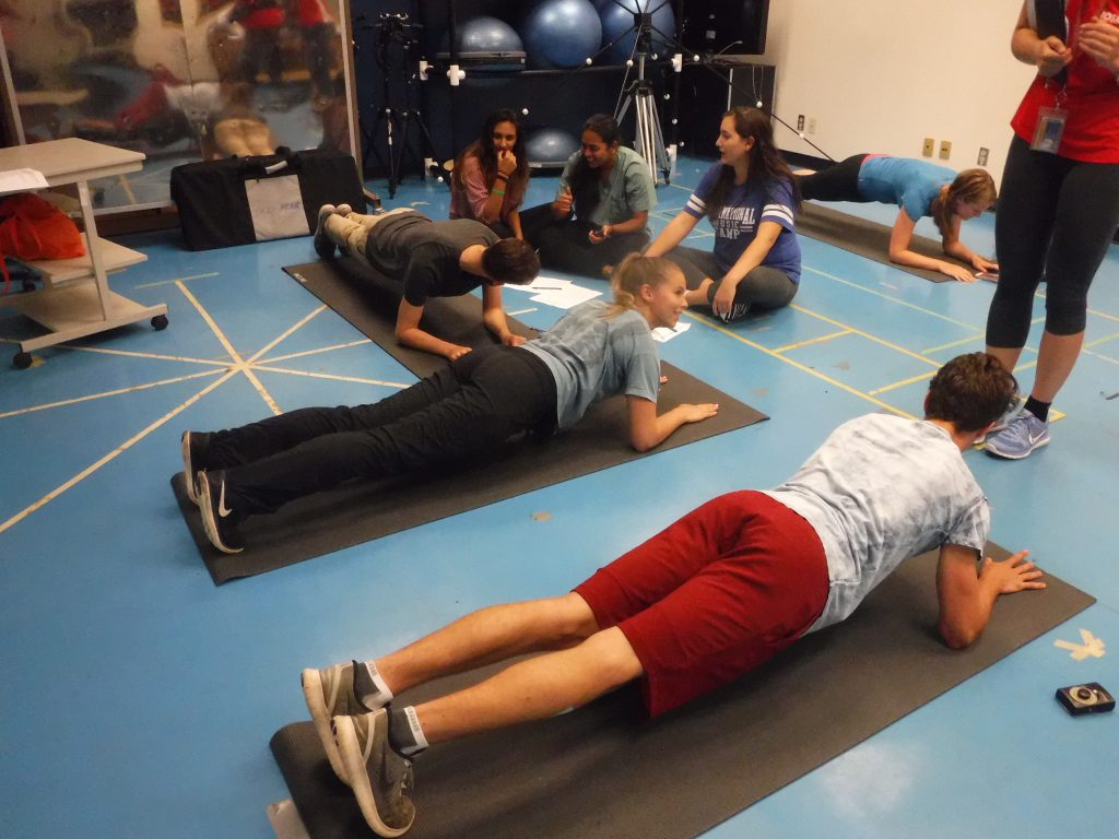 Four campers perform planks in kinesiology classroom while fellow campers and team lead look on