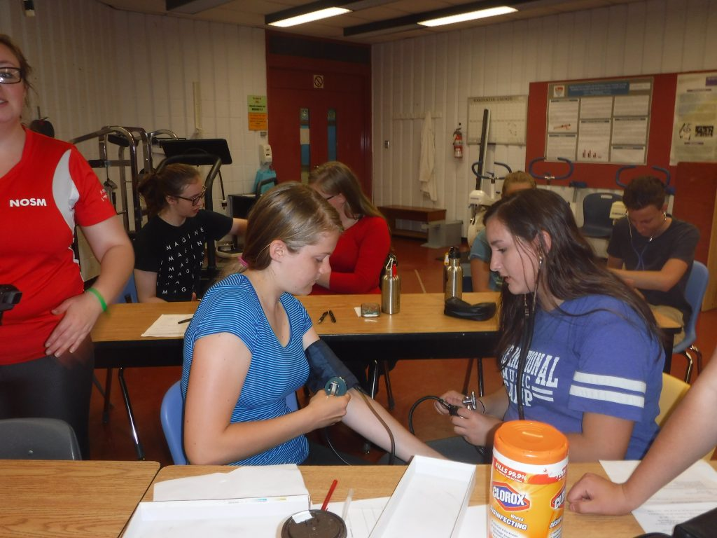 Camper takes blood pressure of fellow camper in kinesiology classroom