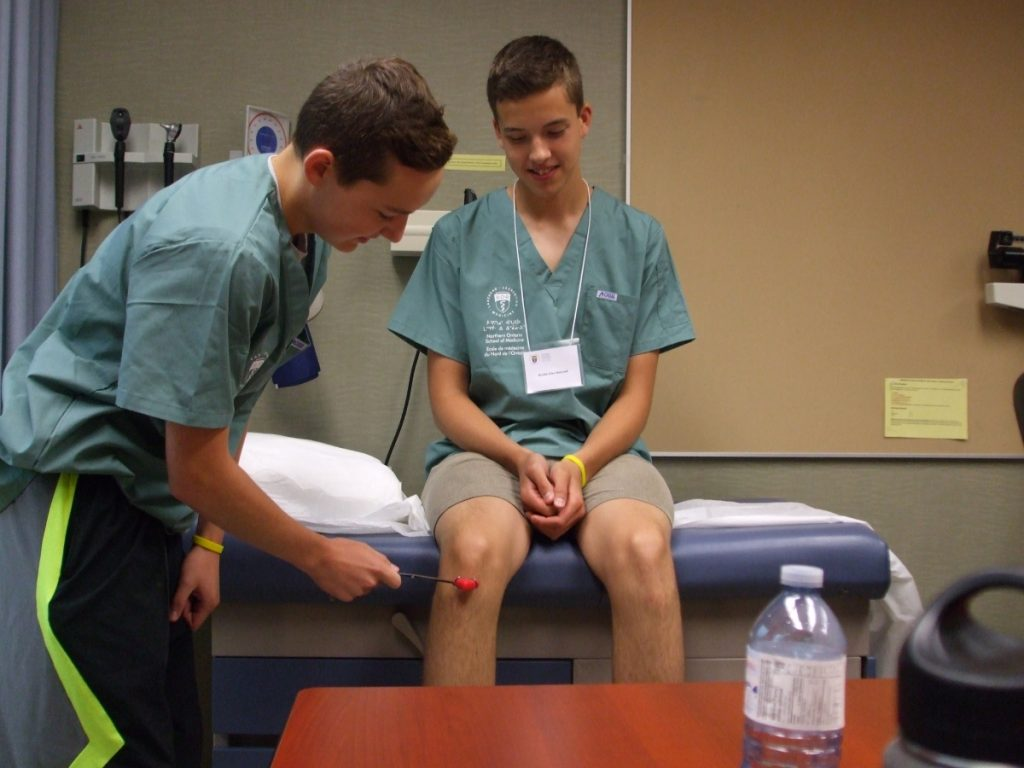 Camper testing knee reflexes of fellow camper in examination room
