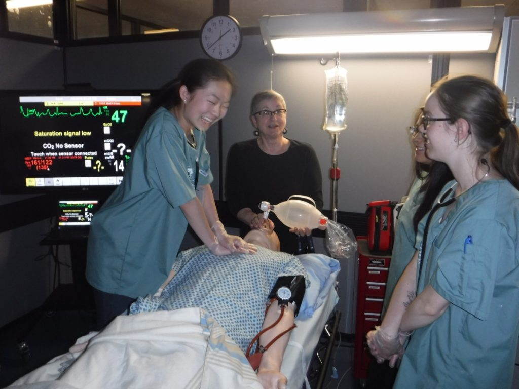 Camper practices CPR on SimMan 3G mannequin while NOSM staff member supervises and two fellow campers observe