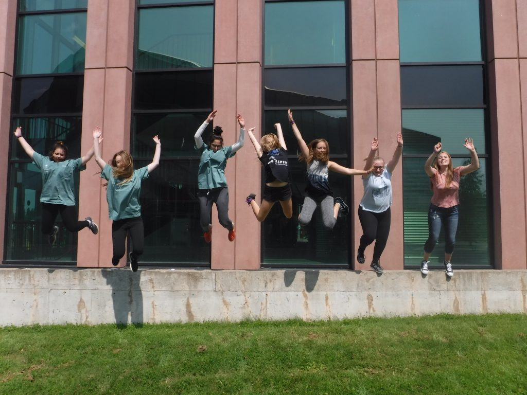 Team purple members jump off short concrete wall in front of ATAC building