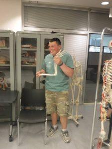 Camper poses with skeleton model's arm