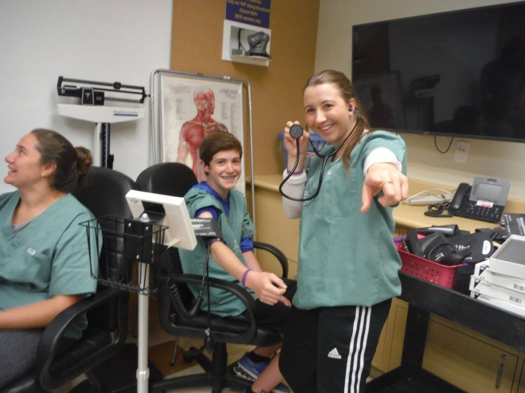 Camper points at camera and smiles with stethescope while fellow camper sitting in chair smiles