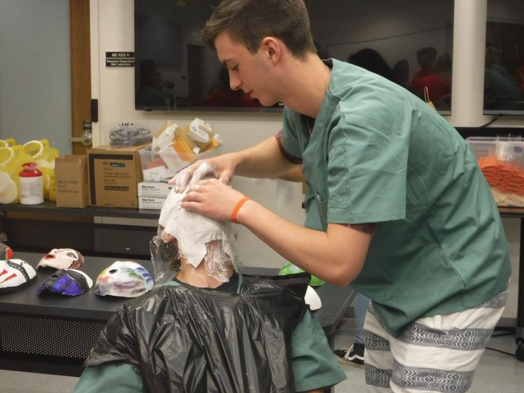 Camper applying mask plaster to fellow camper's face