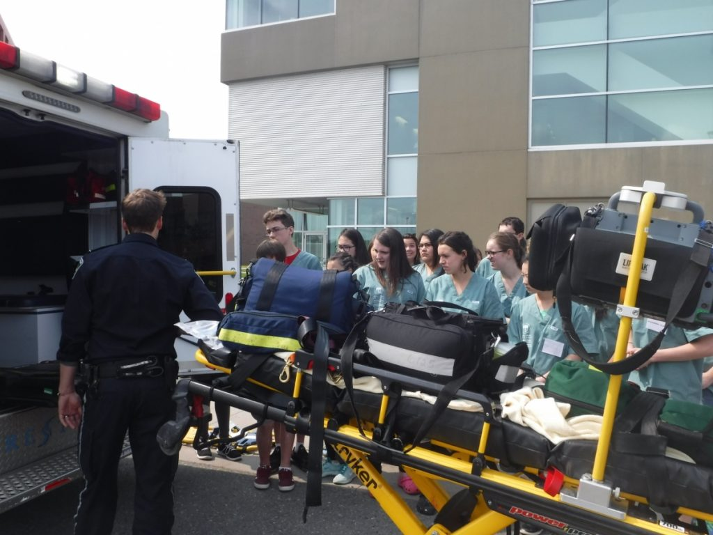 Paramedic showing campers the inside of an ambulance and a stretcher