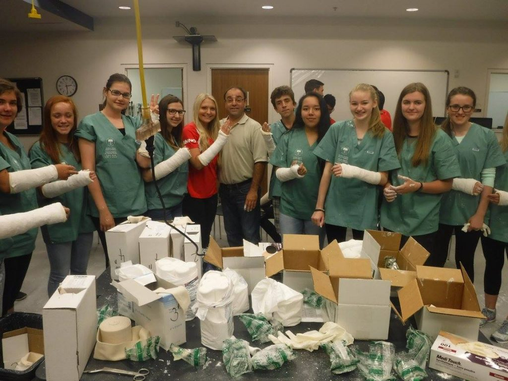 Group photo with campers, team leads, and orthopedic technologist. Campers and team leads are displaying their casted arms