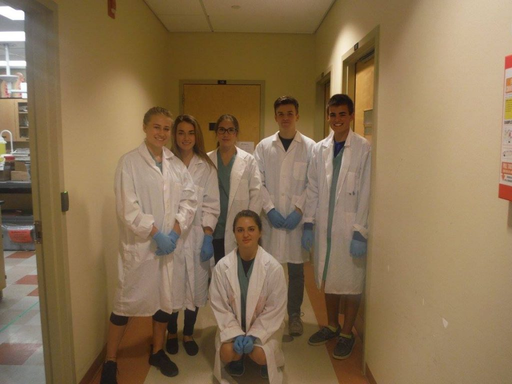 Campers pose for picture while wearing white lab coats and blue latex gloves just outside of wet lab