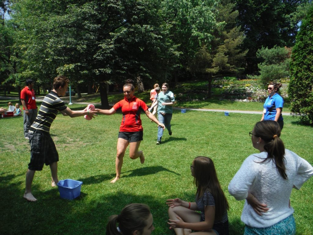 Team lead and campers playing sponge game outside