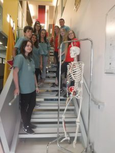 Campers and team leads pose on stair case with skeleton model