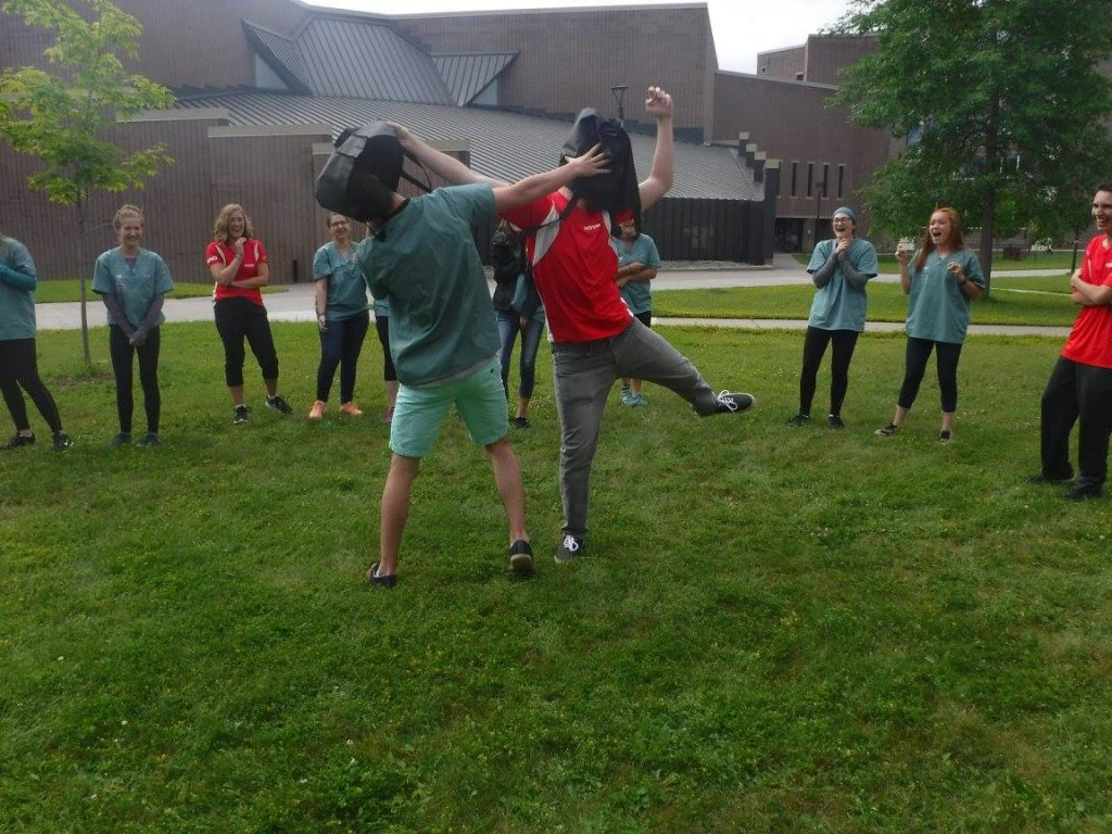Campers stand in circle outside watching two fellow campers try to remove a bag from each others head as an ice-breaking activity