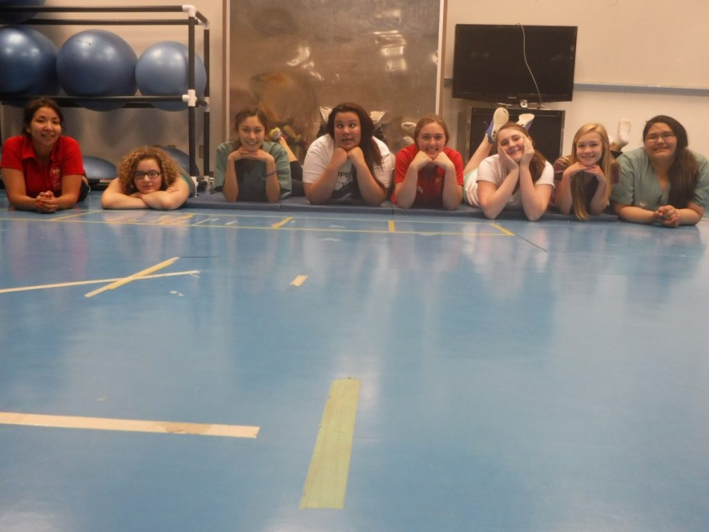 Campers and team lead laying on stomachs on gymnasium floor with chins on their hands and feet in the air for photo