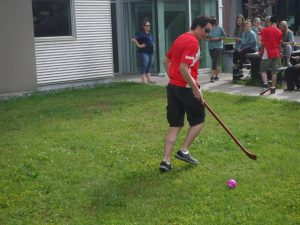 Team Lead plays with a modified hockey stick and ball outside