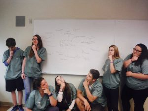 Camper team strikes thoughtful pose in front of a whiteboard