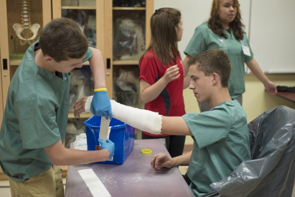 Camper applying casting material to fellow campers arm while team lead talks to camper in background