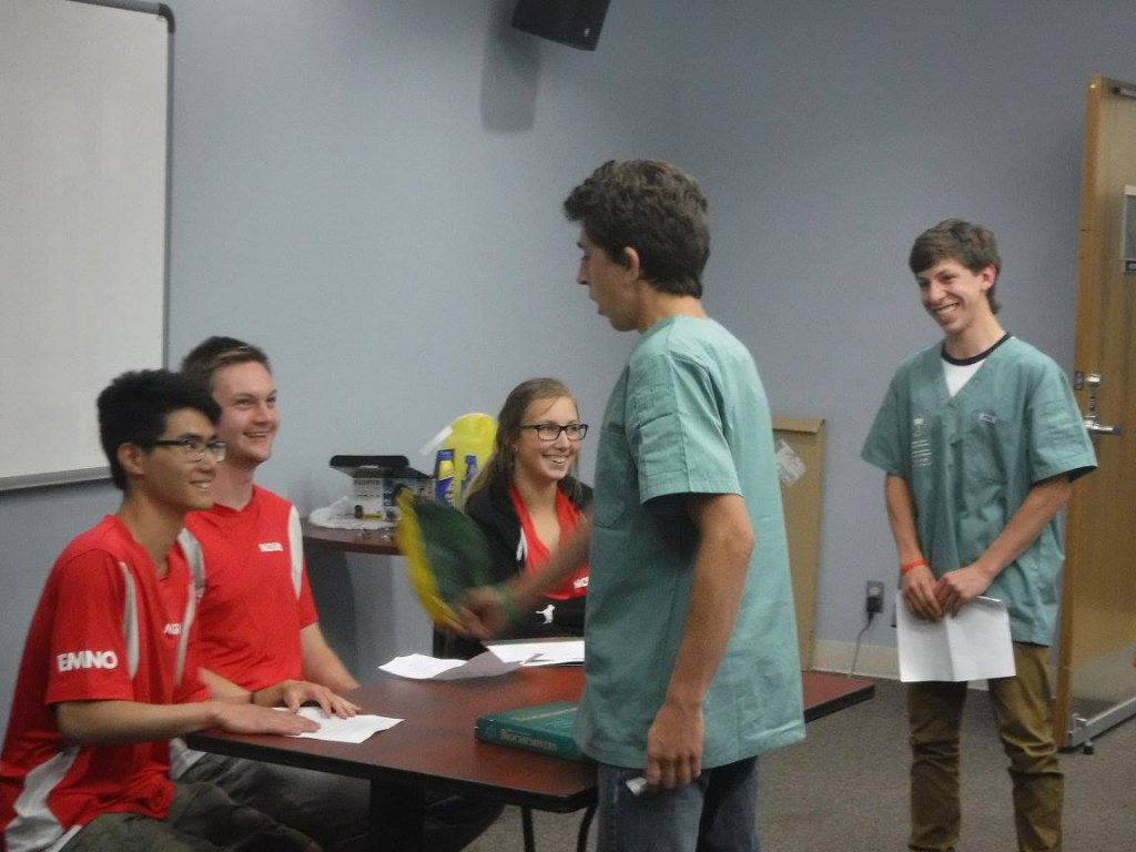 Camper interrogates team leads who are suspects in the investigation while fellow camper grins and looks on