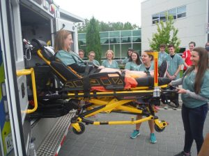 Campers practice lifting EMS stretcher with fellow camper on it into ambulance