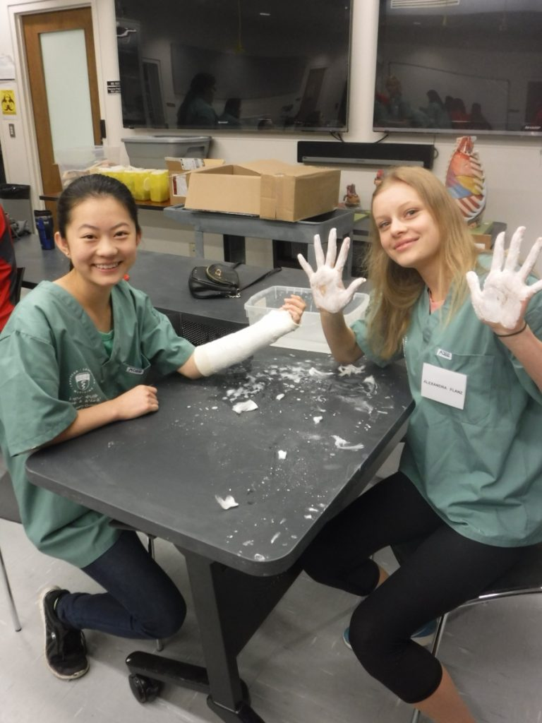 Camper displays hands covered in casting plaster while fellow camper displays completed cast on arm