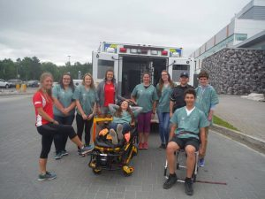 Campers and Team Leads pose for picture with EMS stretcher and ambulance