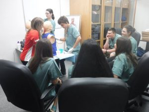 Camper practices inserting a naso-gastric tube into simulation mannequin bust while fellow campers observe