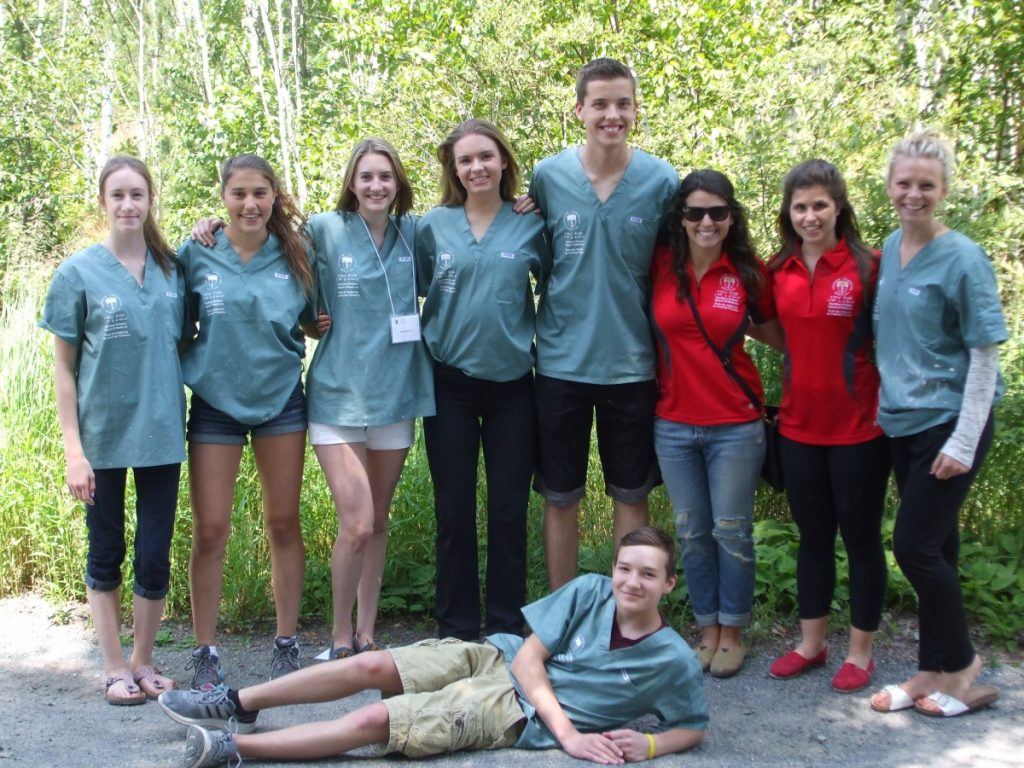 Seven campers and two team leads pose for picture outside with one camper laying on ground leaning up on one elbow