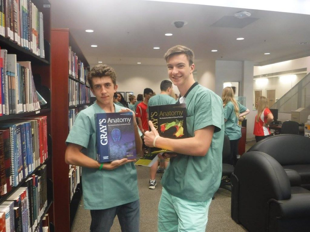 Two campers pose in NOSM library with Gray's Anatomy text books