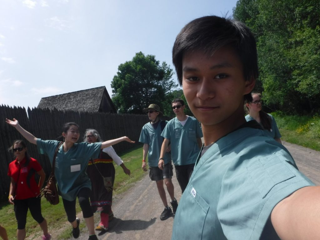 Camper takes selfie with fellow campers walking in the backgound at Fort William Historical Park