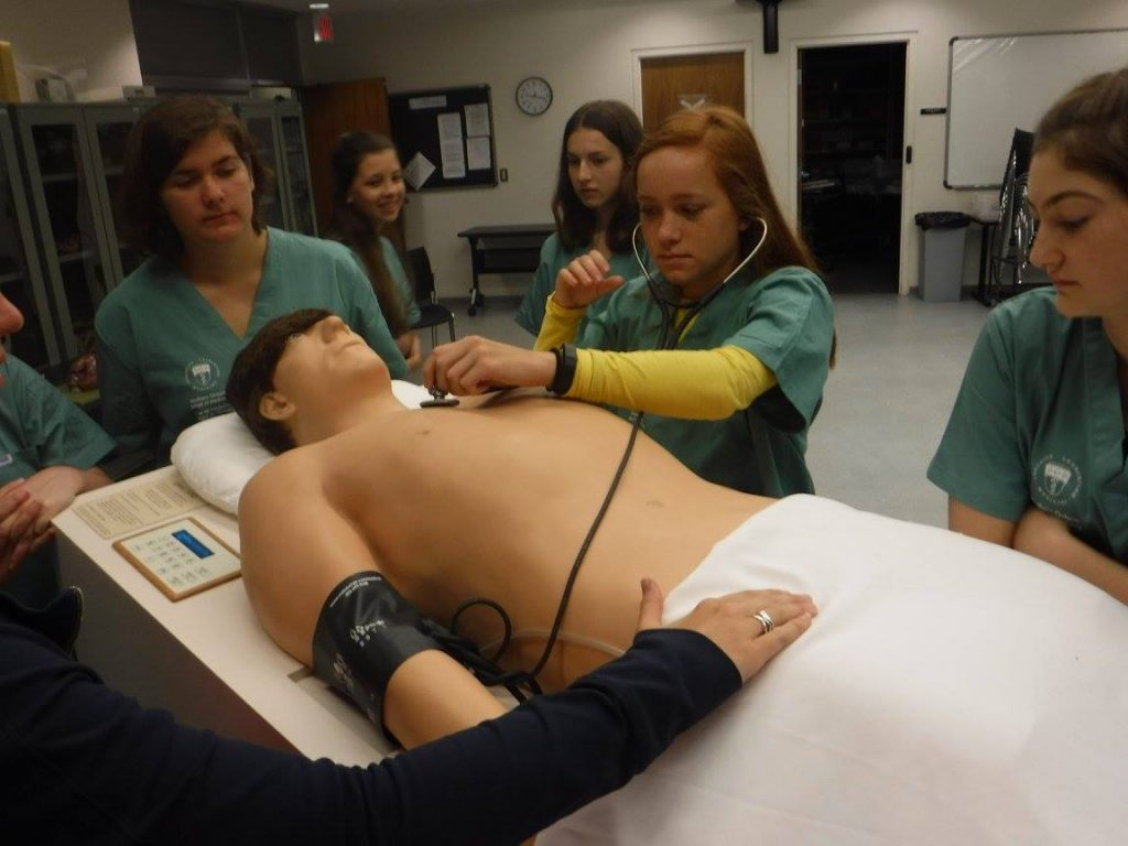 Camper practicing using a stethescope with SimMan 3G mannequin while fellow campers look on