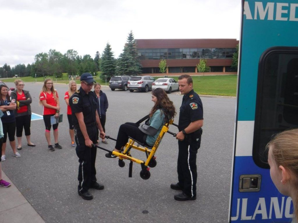 Two paramedics demonstrate carrying a camper in an EMS chair